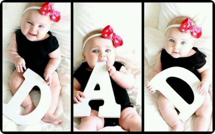 """Niña de ojos azules con letras formando la palabra """"Dad"""""""
