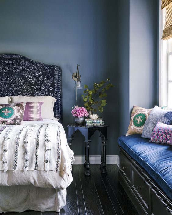 Bedroom designed by Amber Lewis. Blue fabric covered headboard with a white comforter with silver sequens. Decorative pillows on the bed. Dark wood floor with a blue wall. Morrocan style side table with flowers. Window seat with a blue cushion and colorful pillows